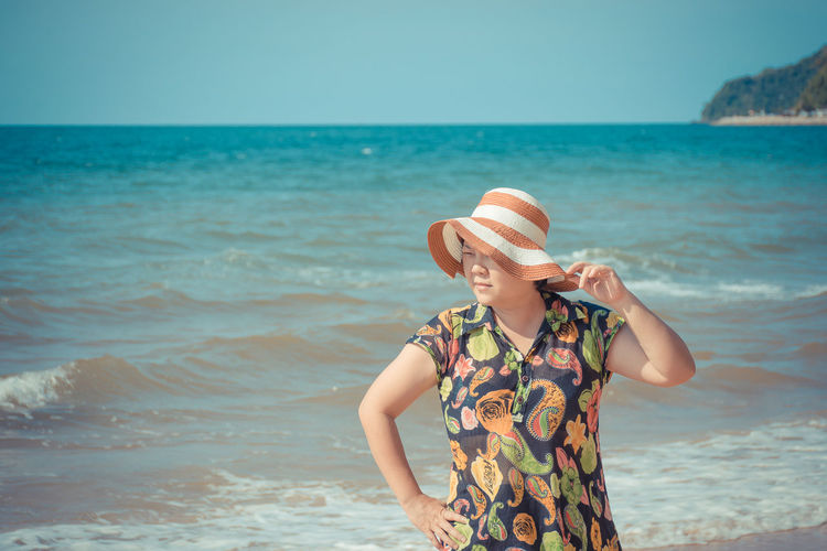 Mature woman standing at beach against clear sky