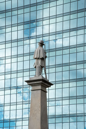 Architecture Built Structure Low Angle View Building Exterior Building No People Day City Glass - Material Outdoors Window Office Building Exterior Sculpture Human Representation Art And Craft Male Likeness Architectural Column Skyscraper Statue Contrast Old And New Confederate Monument