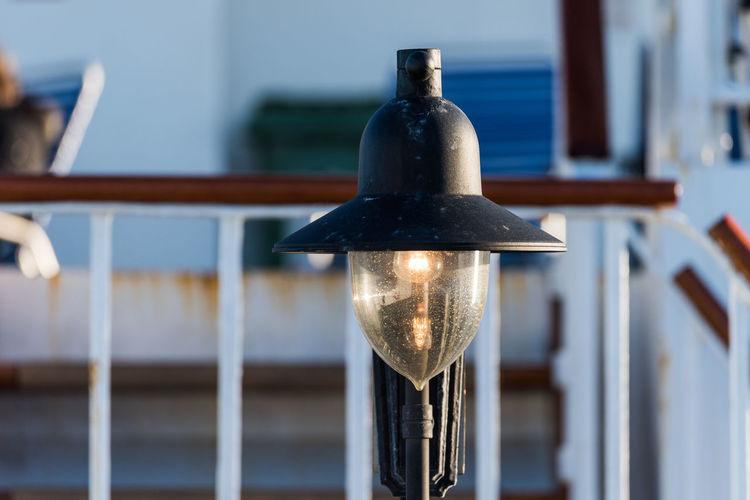 Close-up of illuminated lamp on railing against building