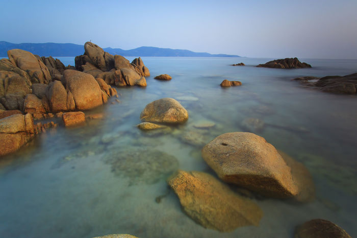 Beach in Corsica with rocks on foreground Beauty In Nature Blue Calm Coastline Corse Day Geology Idyllic Nature No People Non Urban Scene Non-urban Scene Outdoors Physical Geography Remote Rock Rock - Object Rock Formation Scenics Shore Sky Tranquil Scene Tranquility Travel Destinations Water