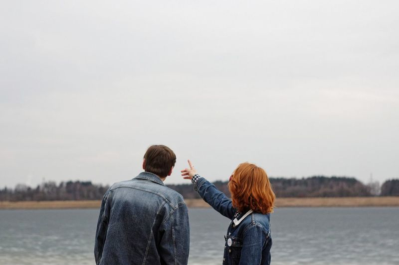 Rear view of couple standing by lake against sky