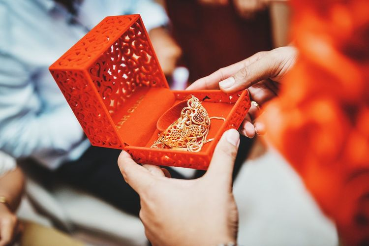 Close-up of hand holding red golden box