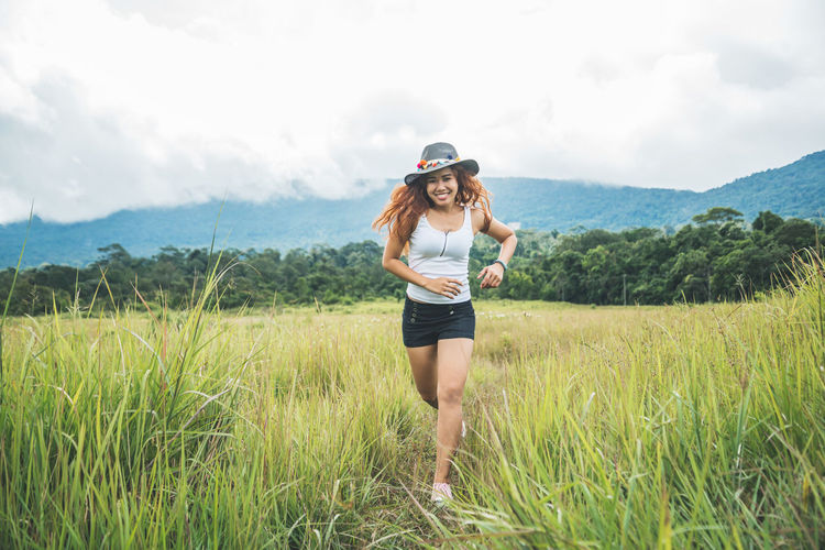 Smiling woman running on field against sky