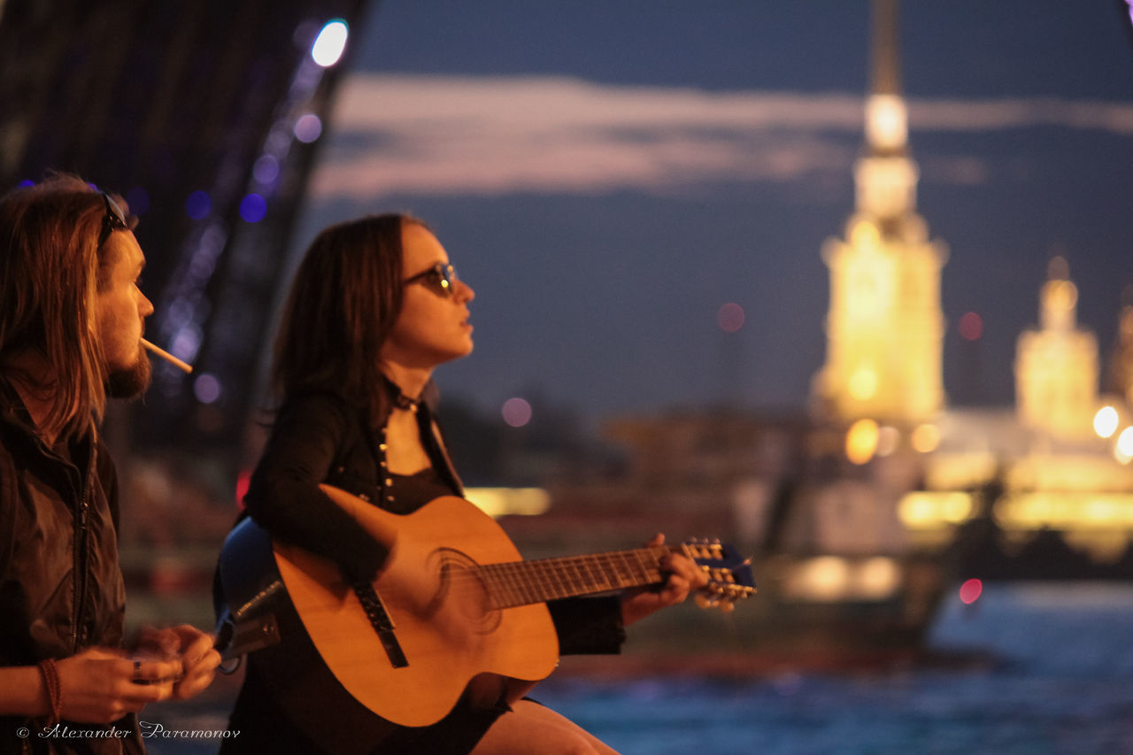 night, guitar, music, focus on foreground, illuminated, arts culture and entertainment, real people, two people, performance, young adult, leisure activity, musician, singing, young women, lifestyles, women, playing, musical instrument, city, outdoors, plucking an instrument, sky, popular music concert, adult, people