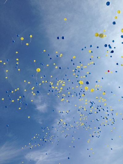 Low Angle View Of Balloons Flying Against Sky