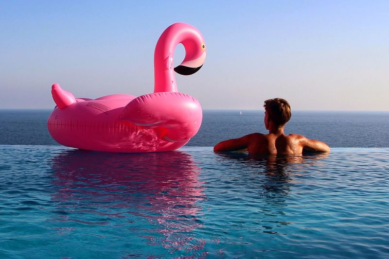 Rear view of shirtless man by inflatable duck in infinity pool against sea