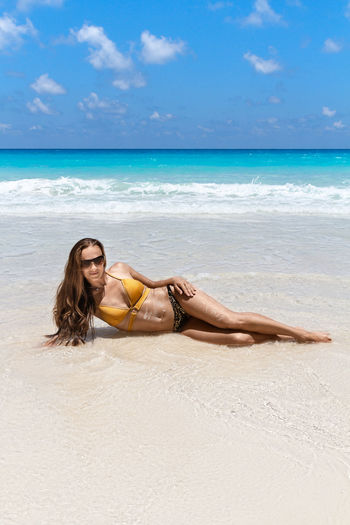 Full length of woman in bikini reclining on shore at beach during sunny day