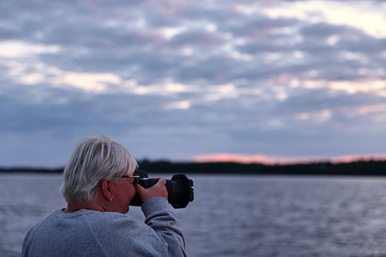 Woman photographing on sea against sky