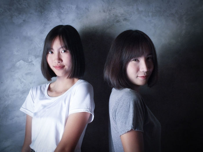 Portrait of smiling young sisters against gray wall