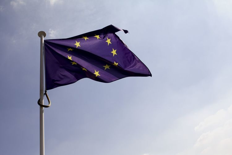 Low angle view of european union flag waving against sky