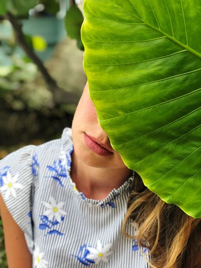Close-Up Of Woman Hiding Behind Leaf