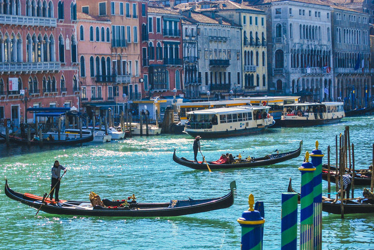People on gondola in grand canal against buildings during sunny day