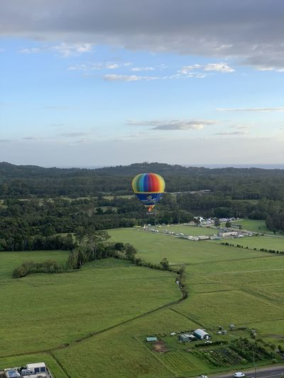 Hot air balloon flying over field against sky