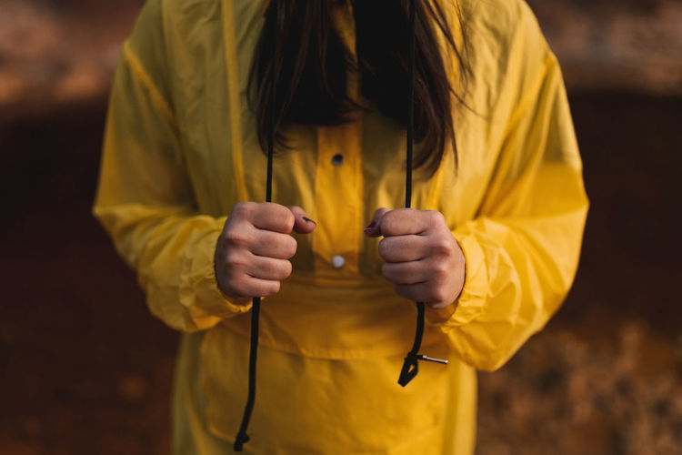 Midsection of woman holding yellow while standing outdoors