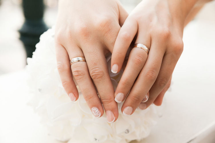 Closeup Of Hands With Wedding Rings Of Two Brides, Homosexual Couple Couple Hands Horizontal Romantic Adult Body Part Bridal Bride Celebration Ceremony Event Homosexual Love Human Body Part Jewelry Love Marriage  Married Nail Newlywed Ring Togetherness Wedding Wedding Ceremony Wedding Ring Women