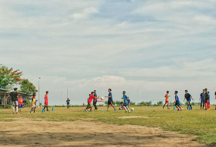 People playing on field against sky