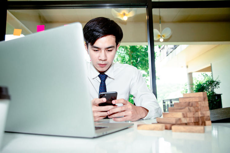 Mid adult man using mobile phone at table