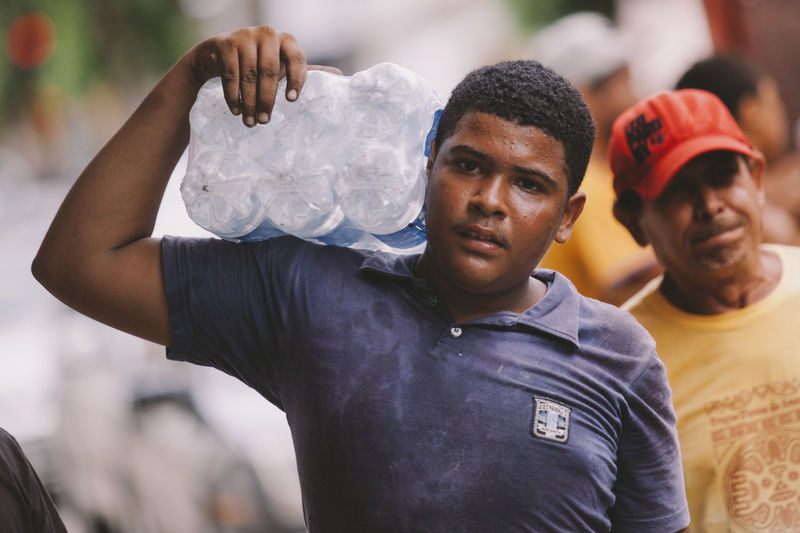 Boy from Governador Valadares help to carry a water supriment in exchange of a few bottles after a mining accident caused by Vale and BHP contamined Rio Doce, a river in Minas Gerais state (the city stayed without proper water to drink for more than a month). Brasil Close-up Front View Person Portrait The Photojournalist - 2016 EyeEm Awards The Portraitist - 2016 EyeEm Awards Water Work Working