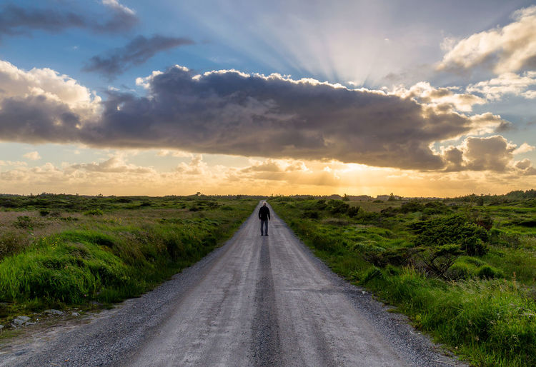 Man standing on road amidst landscape against sky during sunset