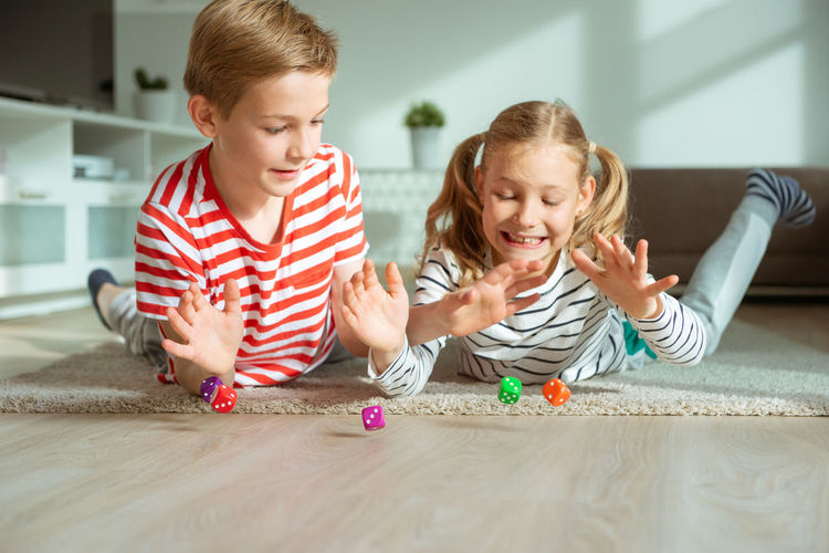 Cheerful siblings playing with dice while lying on carpet at home