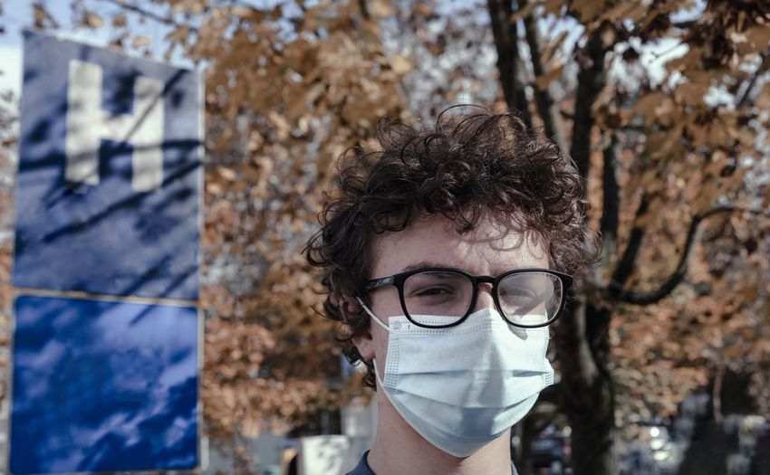 Portrait of boy wearing mask standing outdoors