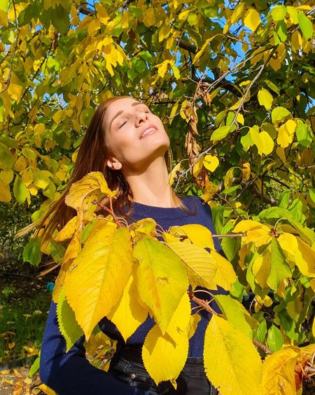 Portrait of smiling woman standing against yellow plants