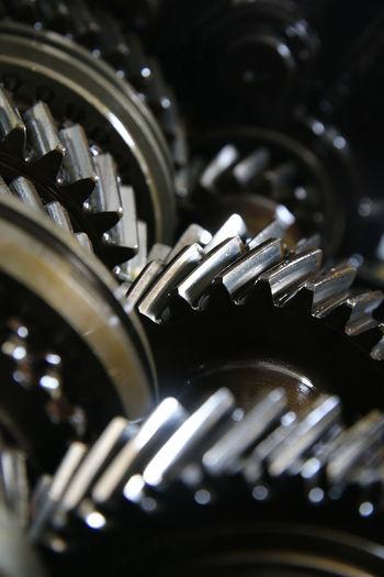 Closeup on gears of machinery Automobile Dark Machine Machinery Mechanical Closeup Engine Engineering Gears Lubricant Mechanics Metal Parts Vehicle