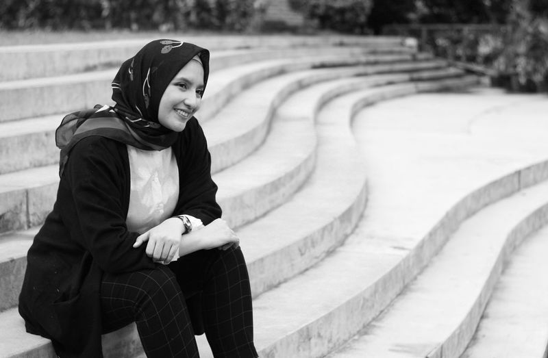 Smiling Woman Wearing Hijab Sitting On Steps
