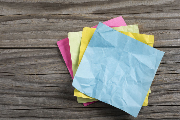 Pile of various crumpled multi colored note papers on an old wooden surface, close up Blue Plank Recycled Multi Colored Table Message Idea Notes Note Reminder Desk Crease Background Wrinkled Copy Space Blank Wooden Wood Colors Colorful Crumpled Paper Adhesive Note Variation Directly Above