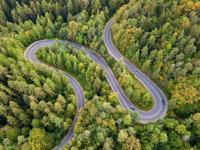Winding road through the forest, from high mountain pass, in autumn season. aerial view by drone