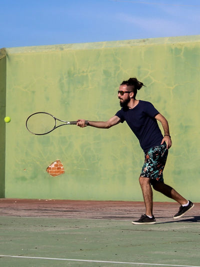 Full length of man playing tennis