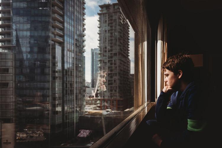 Man looking through window in city