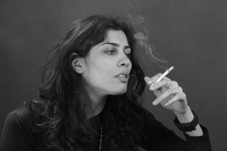 Sad woman smoking cigarette against gray background