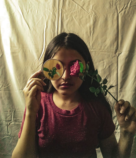 Girl holding flower in front of face against textile
