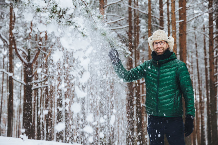 Young woman in snow covered trees