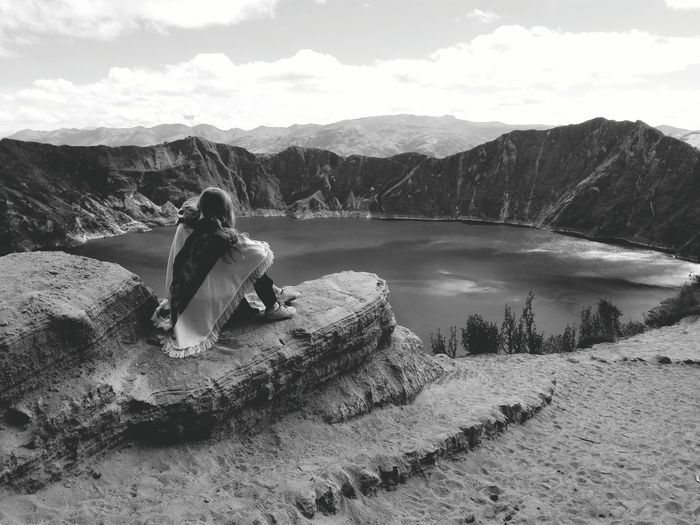Woman Sitting By Crater Lake Amidst Mountains Against Sky