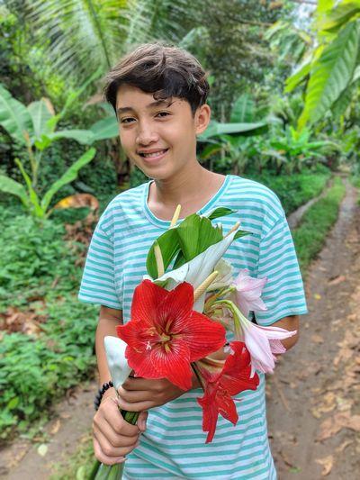 Portrait of smiling teenage boy holding flowers