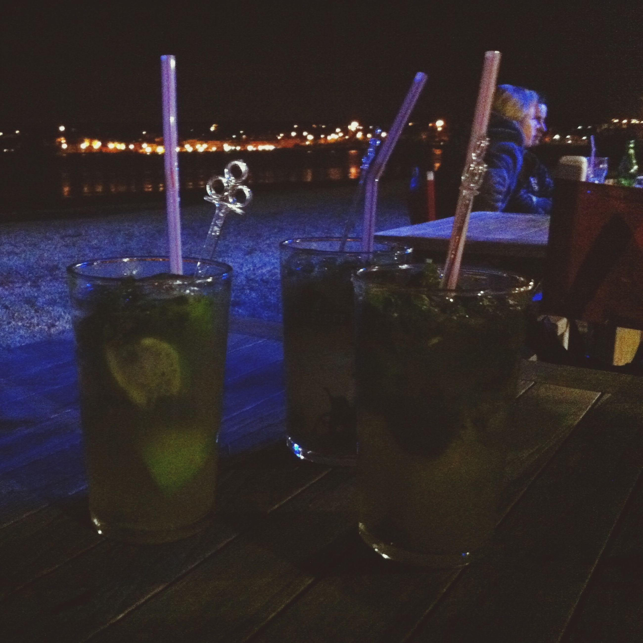 night, water, illuminated, table, reflection, drinking glass, drink, restaurant, swimming pool, refreshment, absence, no people, chair, food and drink, lighting equipment, empty, blue, sea, still life, waterfront