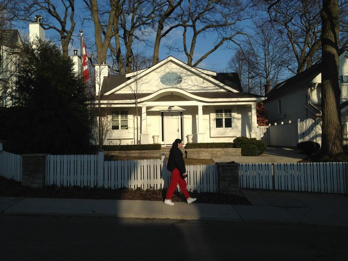 Rear view of woman standing by building against trees