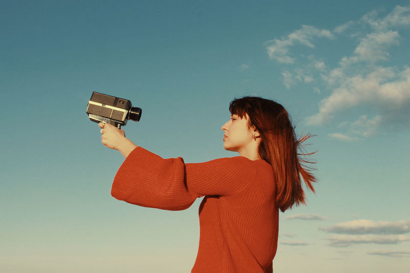 Side view of woman photographing against sky