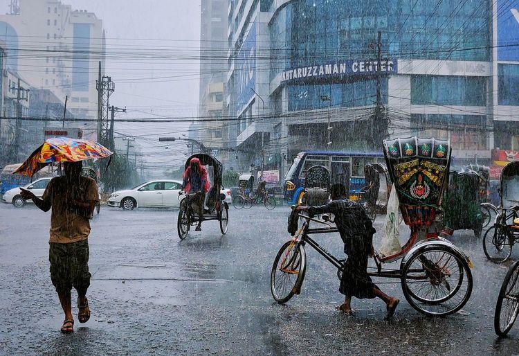 People riding bicycle on wet street during rainy season