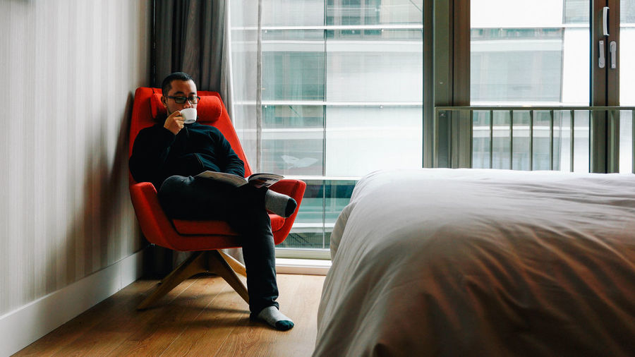 Full length of man drinking coffee while sitting at bedroom