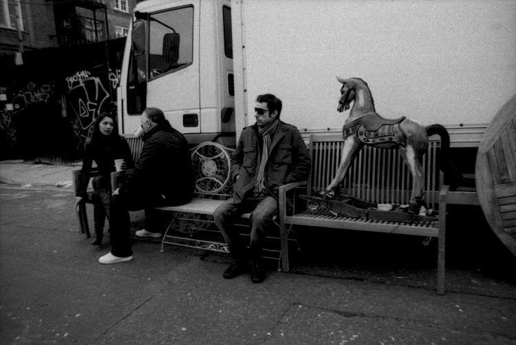 Market people and a Rocking Horse Black And White Photography Casual Clothing City Life Day Documentary Nature Photography Photography Taking Photos A Leisure Activity Lifestyles Market People East End Columbia Road London Sitting Amomgst The Rubbish Outdoors People Photography Portraiture; B/W Photography Reportage Images Taking Photos Photography From My Point Of View Rocking Horse