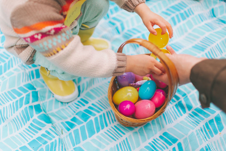People holding easter eggs in basket