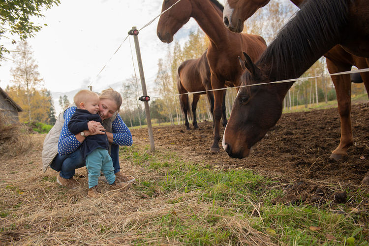 Mother and son playing with horses in ranch