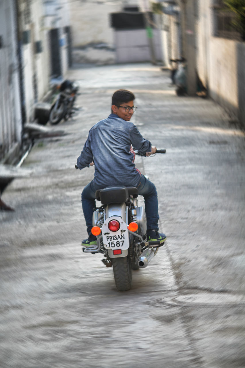 real people, transportation, riding, full length, motorcycle, one person, men, mode of transport, rear view, lifestyles, leisure activity, land vehicle, day, built structure, sitting, outdoors, architecture, young adult, one man only, adult, people