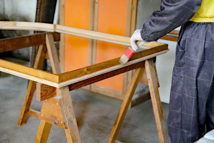 Midsection of carpenter painting wood