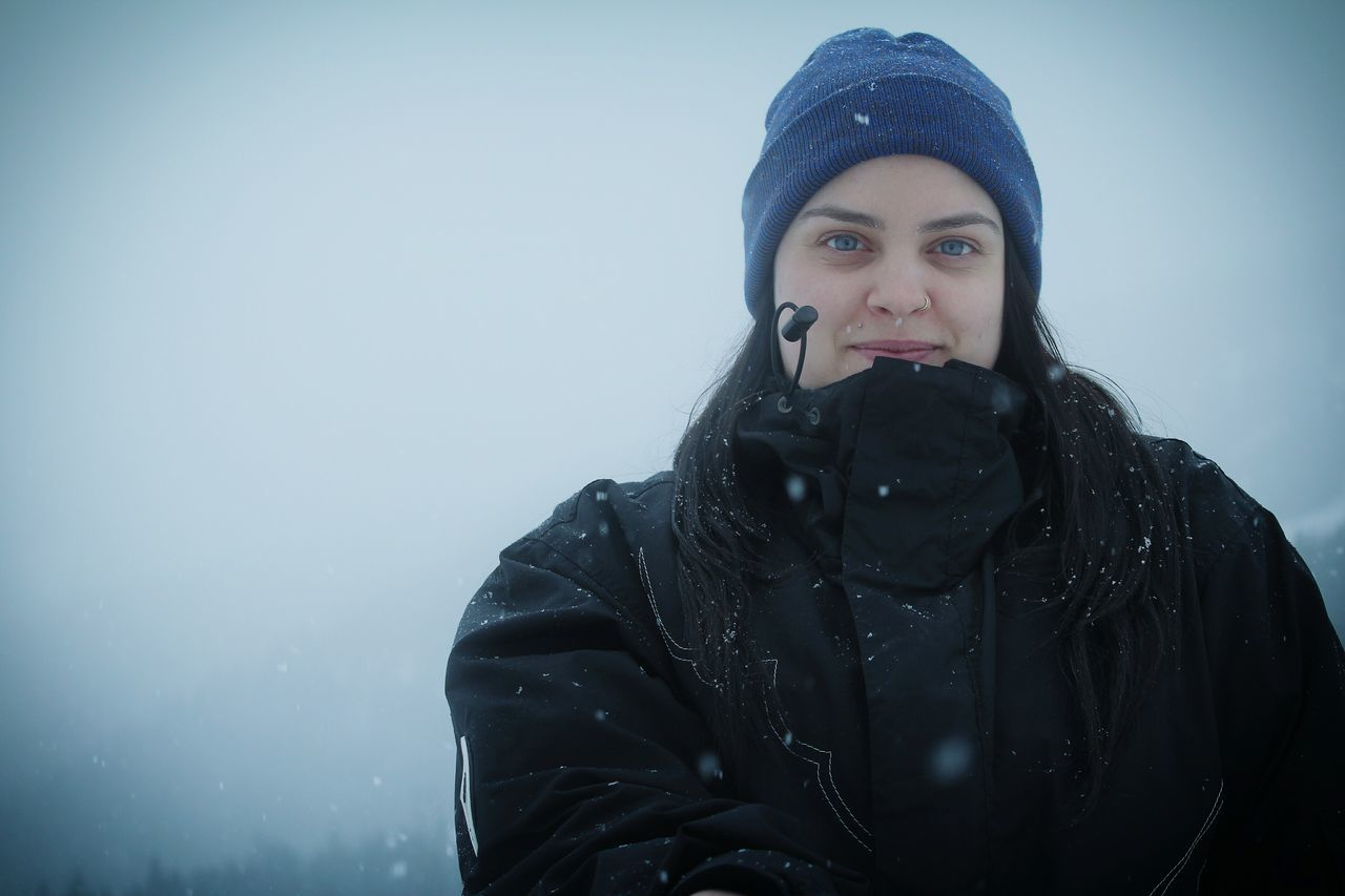 winter, cold temperature, young adult, warm clothing, front view, young women, weather, one person, real people, lifestyles, leisure activity, fashion, black color, confidence, beautiful woman, outdoors, looking at camera, portrait, beauty, snow, day, nature, close-up, sky, people