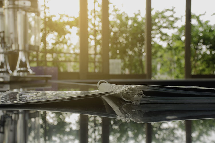 Close-up of menu on glass table with reflection at cafe