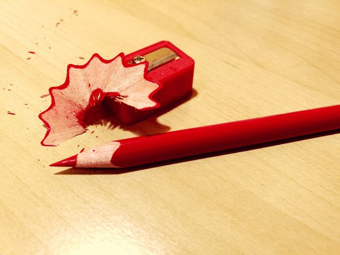 Red pencil with sharpener on wooden table